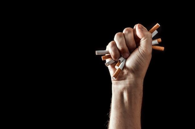 O fundo criativo, mão masculina aperta um punho de um cigarro.
