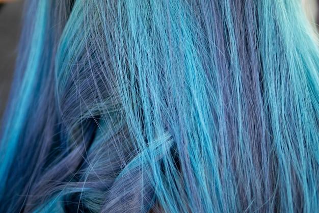 O fundo da cor tingida azul do cabelo do torquoise com técnica do destaque faz o cabelo danificado