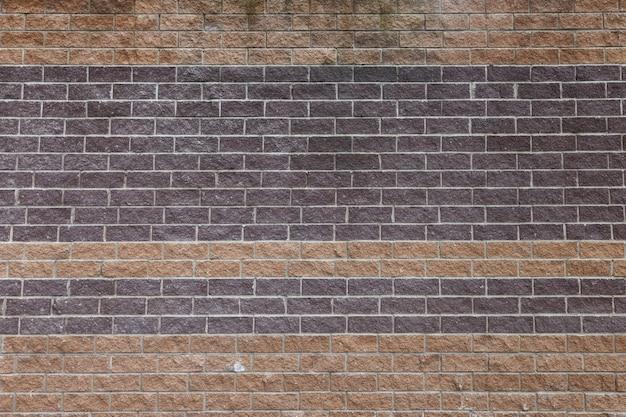 O fundo da parede é feito de tijolos vermelhos e marrons, ampla alvenaria com tinta de construção