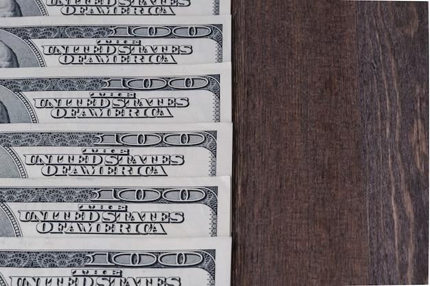 O fundo das peças é de cem notas de dólar, um deitado sobre a mesa de madeira escura.