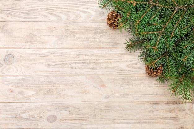 O fundo de madeira cinzento do natal com quadro e cones da árvore de abeto copia o espaço. vista superior, espaço vazio