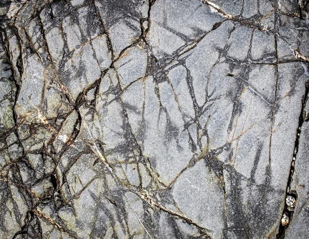 O fundo de pedra preto cinza escuro ou textura.