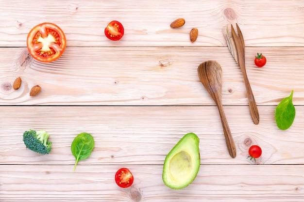 O fundo do alimento e o conceito da salada com os ingredientes crus lisos colocam no fundo de madeira branco.