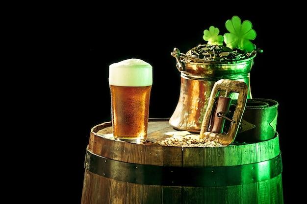O fundo do barril de madeira com muitas moedas de ouro e uma grande caneca de cerveja com um laço verde. plano de fundo para a celebração do dia de são patrício e o conceito de feriado religioso