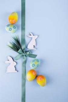 O fundo do feriado da páscoa com galinha pintada colorida eggs o coelho de madeira decorativo e flores e fita. configuração plana