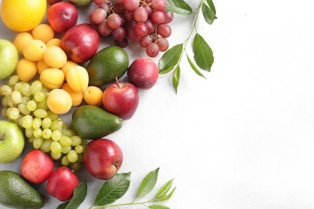 O fundo do fruto com maçãs, uvas, abricós, pêssegos e abacate na opinião superior do fundo branco copia o espaço.