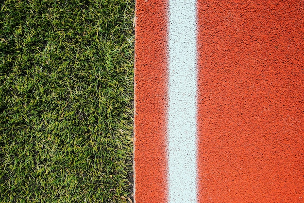 O fundo é composto por uma capa de esteira e grama artificial verde. linhas brancas marcadas no campo de esportes. textura com temática de esportes.