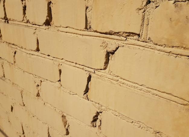 O fundo é feito de tijolos antigos pintados de amarelo.