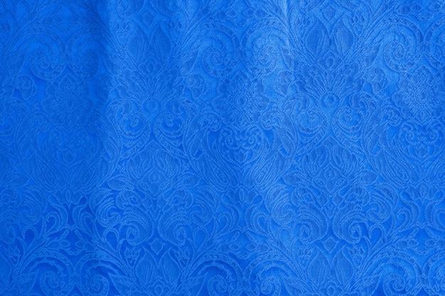 O fundo é feito de um desenho abstrato de tapeçaria de material têxtil azul, a textura de uma peça de roupa.