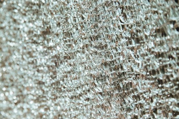 O fundo é feito de vidro quebrado em pequenos pedaços. reflexo dos raios do sol na superfície. a textura de um espelho quebrado. um padrão incomum.
