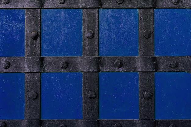 O fundo é pintado com tinta azul com vigas de metal e rebites.