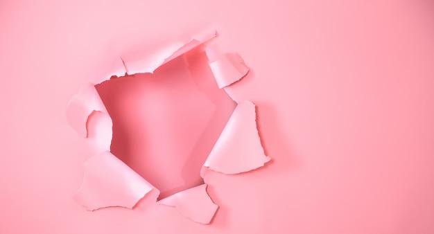 O fundo é rosa com um furo para propaganda