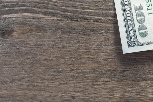 O fundo é uma árvore texturizada escura, na borda da borda cem notas de dólar.