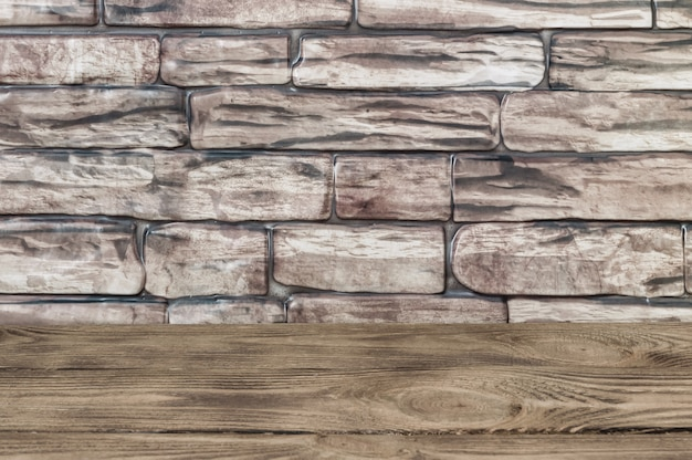 O fundo é uma parede de grandes tijolos marrons e tábuas de madeira.