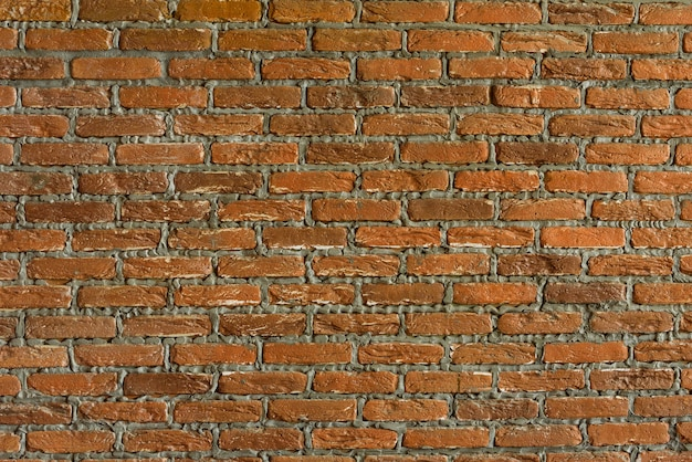 O fundo é uma velha parede de tijolos a parede é feita de tijolos de cerâmica vermelha