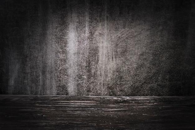 O fundo escuro de uma parede texturizada e um piso de concreto.