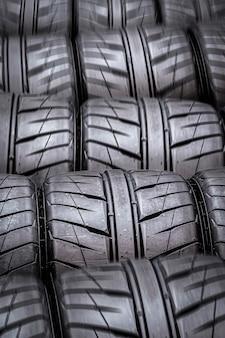 O fundo preto dos novos pneus desportivos com piso de chuva.