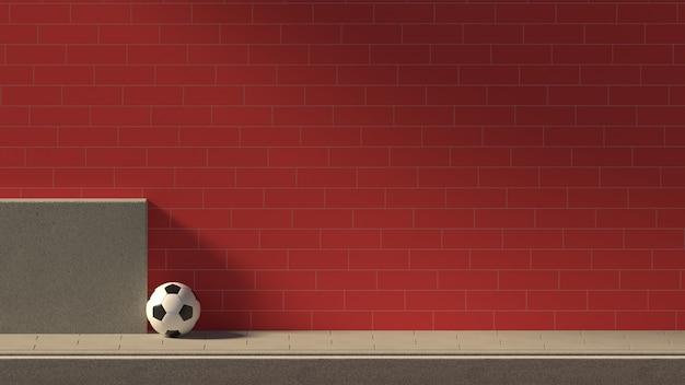 O futebol na frente de uma parede de tijolos ao lado da estrada mínima