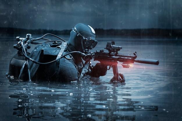 O fuzileiro naval sai da água e se move em direção ao alvo com as armas nas mãos.