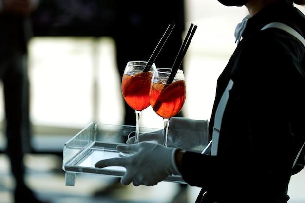O garçom carrega dois copos de coquetéis vermelhos em uma bandeja