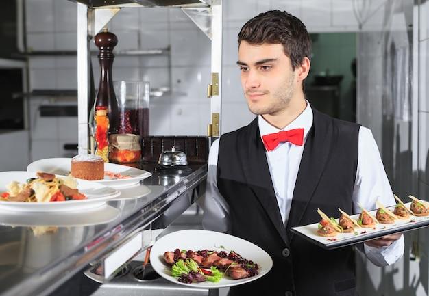 O garçom com os pratos preparados na cozinha do restaurante.