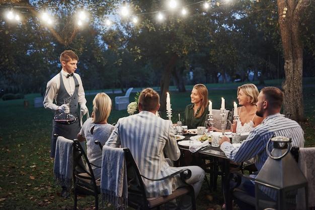 O garçom com vinho está aqui. amigos têm reunião à noite. nice outside restaurant