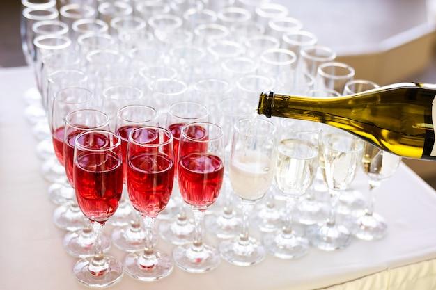 O garçom derrama champanhe em copos na rua - catering de casamento