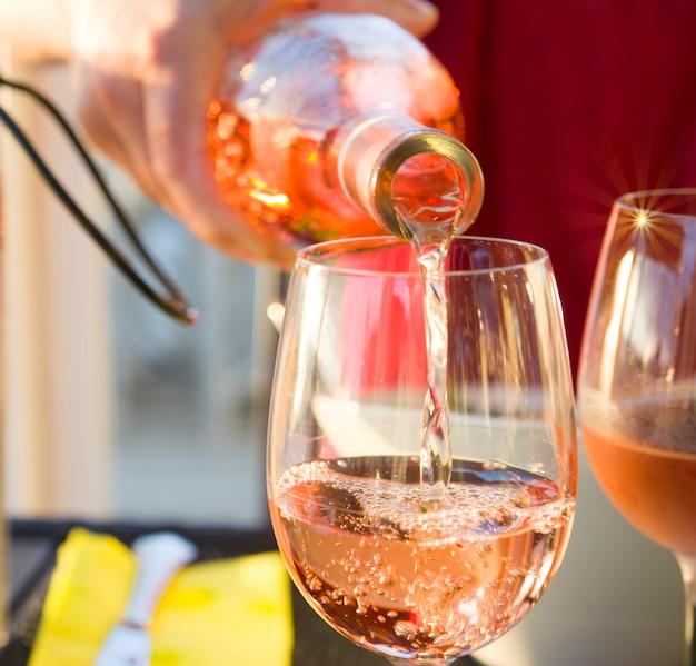 O garçom derrama o vinho francês rosa no copo sparks