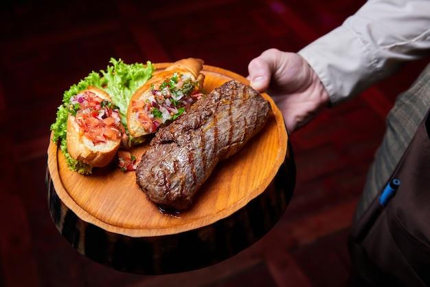 O garçom segura lombo de vitela com molho de tomate na bruscheta em um prato de madeira