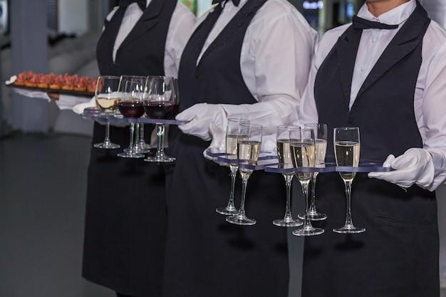 O garçom segura taças com vinho branco e tinto no evento