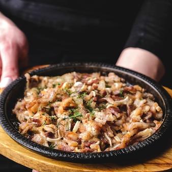 O garçom segura um prato com orelhas de porco com molho e alho.