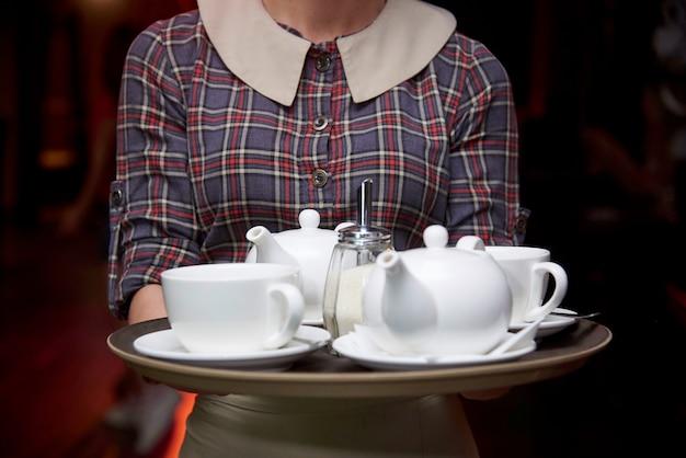 O garçom segura uma bandeja com chaleiras e xícaras quentes.