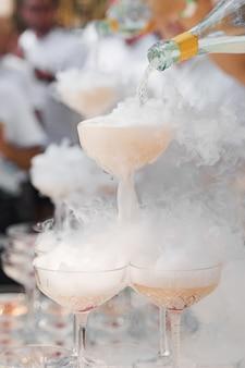 O garçom serve champanhe em taças de cristal com gelo seco e fumaça branca de perto