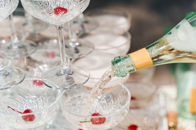 O garçom serve champanhe em taças de cristal de perto
