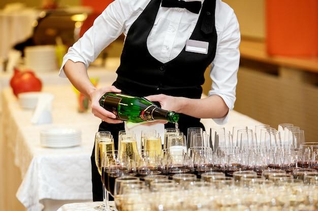 O garçom serve champanhe em taças de cristal