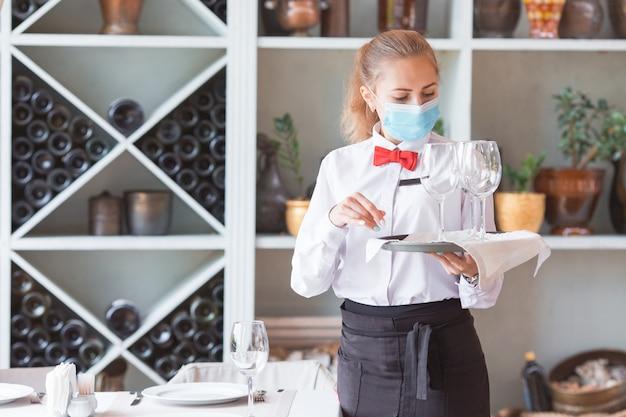 O garçom serve uma mesa em um café com uma máscara protetora.