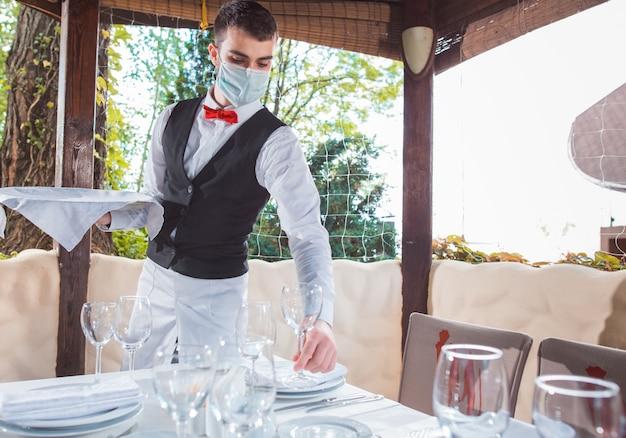 O garçom trabalha em um restaurante no terraço de verão