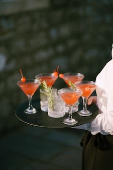 O garçom traz coquetéis em uma bandeja com coquetéis de manhattan com cerejas e vodka com limonada e