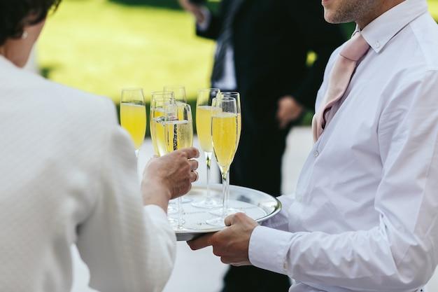 O garçom vestido de branco carrega óculos com champanhe