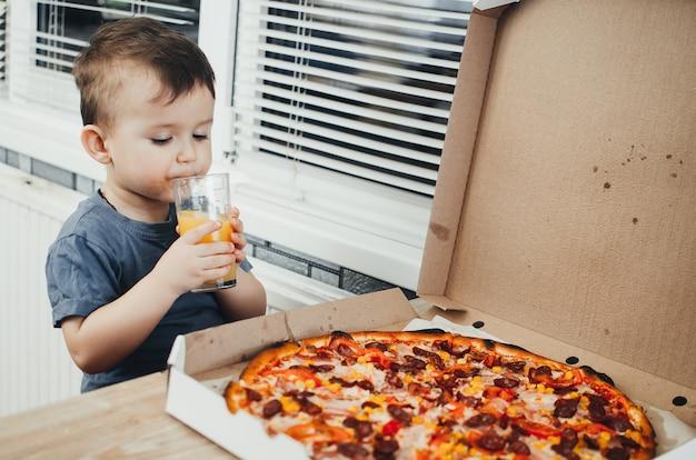O garotinho come ele mesmo uma pizza enorme e nociva na cozinha e bebe suco, muito gordo e nocivo