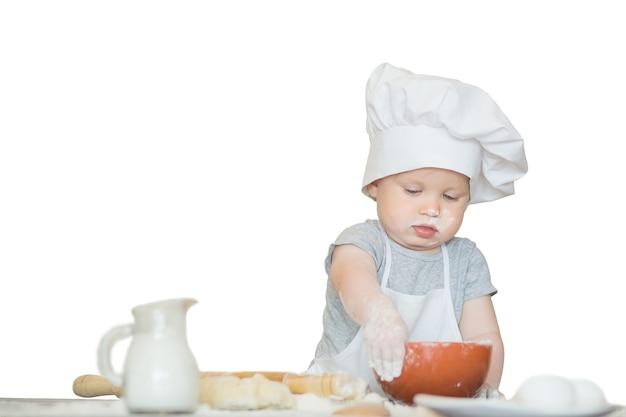 O garotinho em um terno de cozinheiro esculpe a massa o copeiro do bebê faz o jantar em um terno de chef