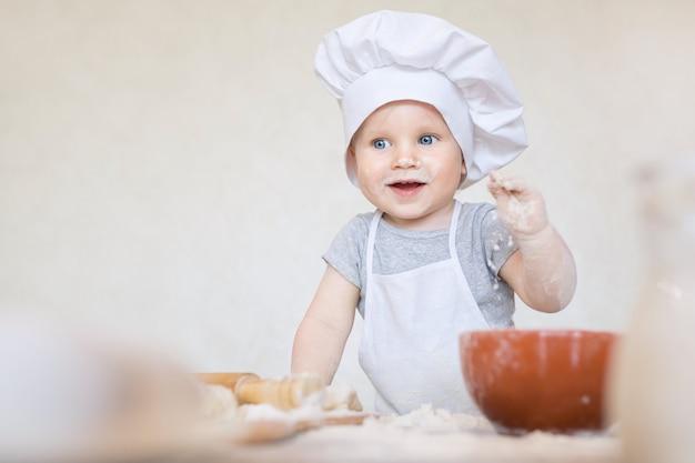 O garotinho em um terno de cozinheiro esculpe a massa o pequeno garoto de cozinha faz o jantar em um terno de chef