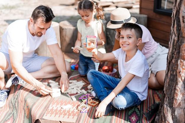 O garotinho mostra o brinquedo do construtor montado, sorri satisfeito com o resultado do seu trabalho, passa o tempo feliz com a família, senta no quintal de verão