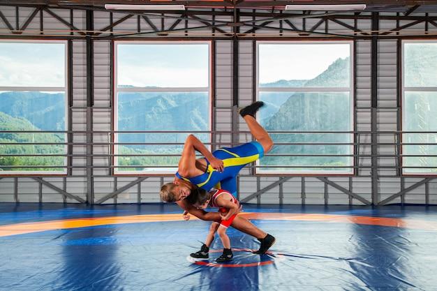 O garotinho no lutador de meia-calça esportiva joga sobre o quadril lutador masculino adulto em um tapete de luta livre no ginásio.