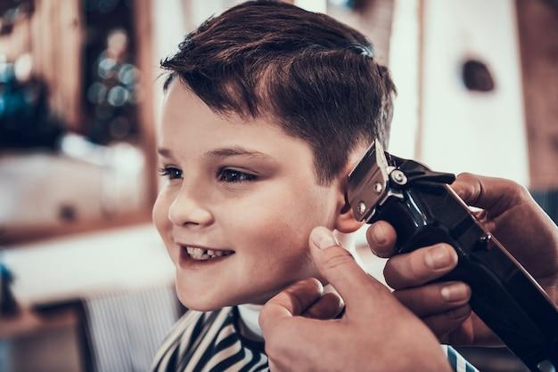 O garotinho sorri quando seu cabelo é cortado.