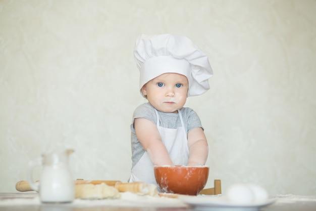 O garotinho vestido de cozinheiro esculpe a massa. bebê fazendo jantar em traje de chef