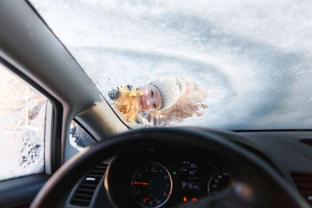 O garoto ajuda e raspando neve e gelo da janela do carro