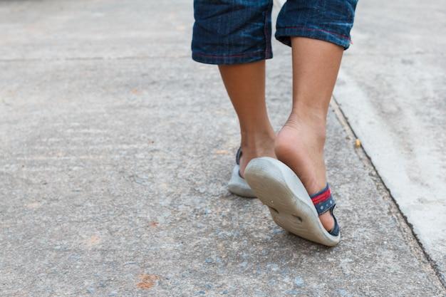 O garoto andando na estrada com sapatos sandálias. conceito de passo a pé