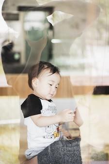 O garoto brincando com a mãe em casa com sombra do pai atirando câmera passar através do vidro.