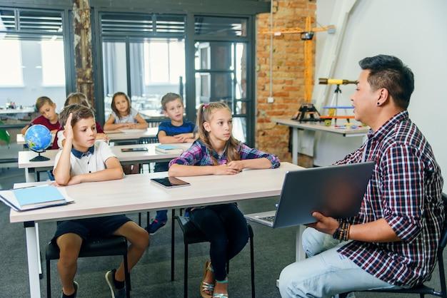 O garoto da escola senta-se atrás da mesa junto com os colegas e levanta a mão para fazer perguntas ao professor durante a aula na escola primária.